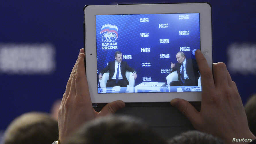 Russia's President Vladimir Putin (R) and Prime Minister Dmitri Medvedev are seen on a screen of a tablet computer during a meeting in the Moscow region, Oct. 3, 2013.