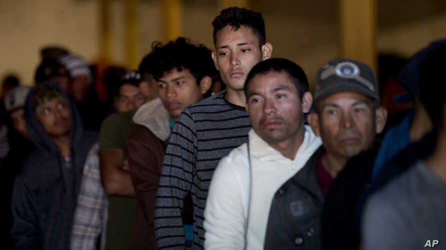 Honduran migrants stand in line for breakfast inside an empty warehouse that opened its doors to migrants in downtown Tijuana, Mexico, Dec. 18, 2018. The owner opened the warehouse for two months, after it had been empty for years, so some migrants d