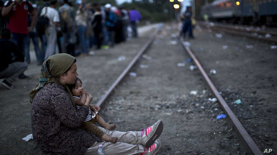 An Afghan refugee woman holding her daughter rests while waiting to board a train heading to the Austrian border, in Roszke, southern Hungary, Sept. 14, 2015.