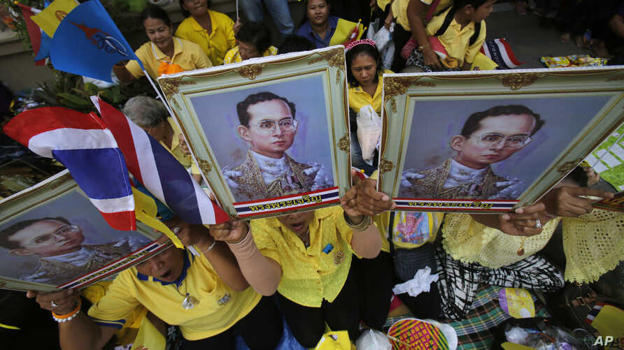 FILE - Supporters hold a portrait of Thai King Bhumibol Adulyadej in Bangkok, Thailand, May 10, 2015.