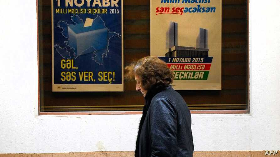 A woman walks past electoral posters in Baku on October 31, 2015, a day ahead of the parliamentary election in Azerbaijan.