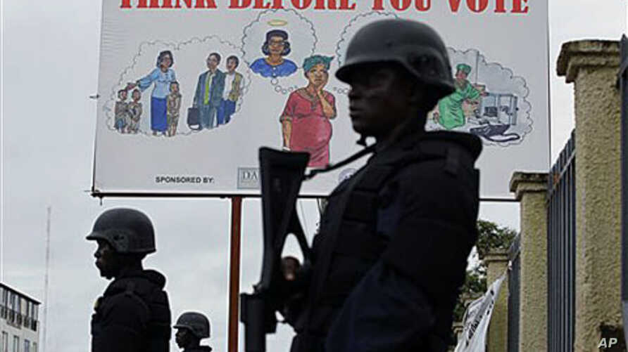 Liberian police equipped with riot gear stand guard outside the headquarters of the National Elections Commission as the NEC prepared to announce the first partial presidential election results, in Monrovia, Liberia, Oct. 13, 2011.