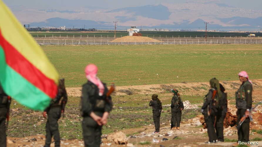 Kurdish members of the Self-Defense Forces stand near the Syrian-Turkish border in the Syrian city of al-Derbasiyah during a protest against the operations launched in Turkey by government security forces against the Kurds, Feb. 9, 2016.