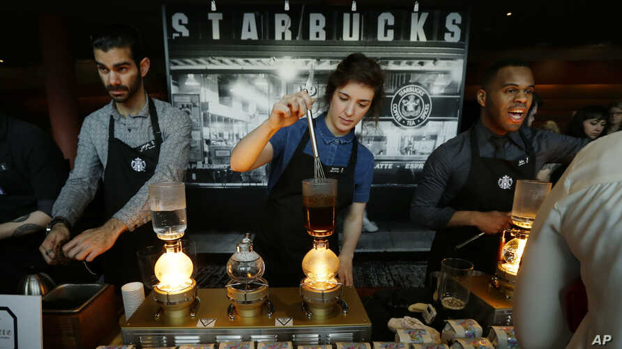 FILE - Starbucks employees prepare coffee in the lobby of the company's annual shareholders meeting in Seattle, Washington, March 23, 2016.