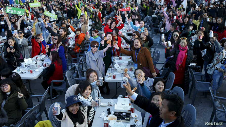 Chinese tourists are seen enjoying canned drinks and fried chicken during an event organized by a Chinese cosmetics company at a park in Incheon, South Korea, March 28, 2016.