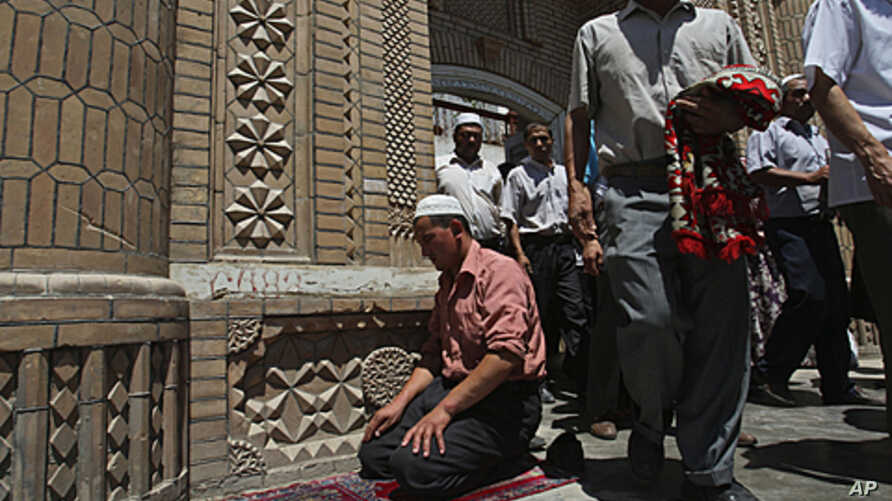 In this Friday, July 10, 2009 file photo, Muslim worshipers come out of a mosque after noon prayers in Kashgar in China's restive Xinjiang province, where new violence erupted on Sunday, July 31, 2011.