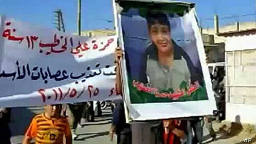 An image grab taken from YouTube on May 28, 2011, shows a Syrian man holding a picture of 13-year-old boy Hamza al-Khatib during his funeral on May 25, 2011 in the flashpoint region of Daraa, Syria