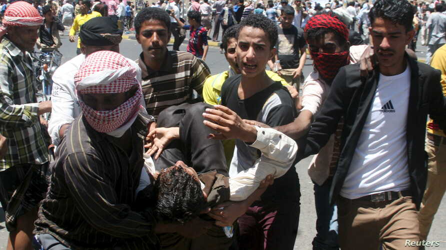 Anti-Houthi protesters carry an injured fellow protester during clashes with Houthi fighters in Yemen's southwestern city of Taiz, March 22, 2015.