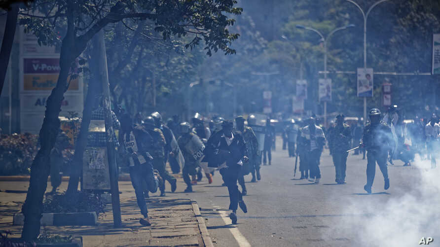 Opposition protesters, center, run from riot police and tear gas at a demonstration in Nairobi, Kenya, Sept. 26, 2017.