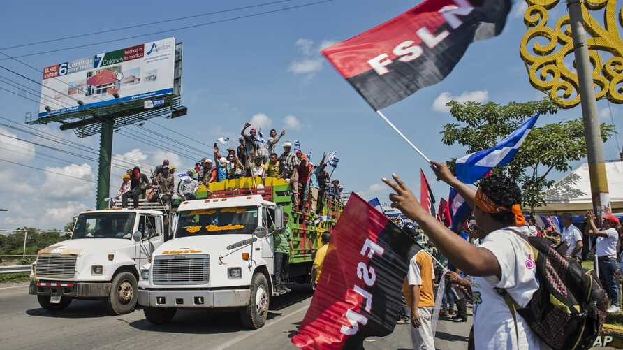 FILE - Supporters of Nicaragua's President Daniel Ortega wave flags of the Sandinista National Liberation Front as farmers opposed to the construction of Nicaragua's transoceanic canal join a national protest against the project, in Managua, Nicaragu