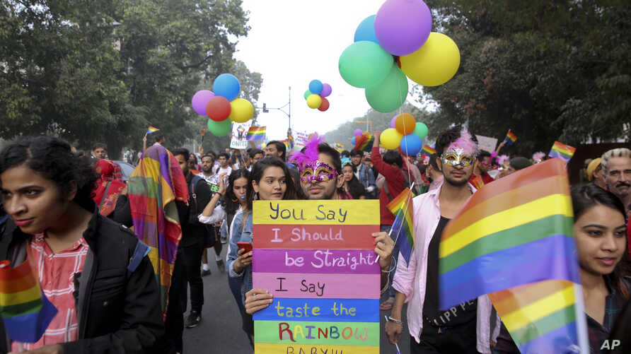 Gay rights activists and their supporters hold colorful balloons and placards as they participate in a gay pride parade in New Delhi, India,  Nov. 12, 2017.