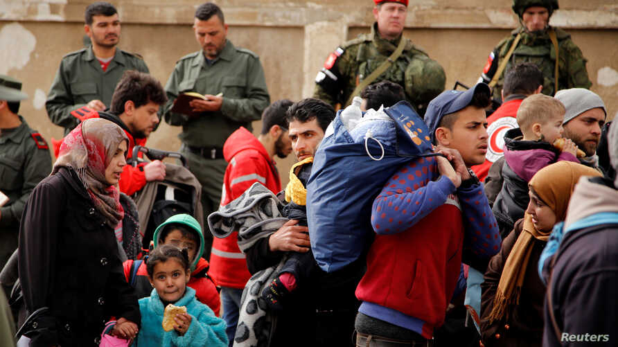 Syrian army soldiers (rear L) and Russian soldiers (rear R) look on as rebel fighters and their families evacuate the besieged Waer district in the central Syrian city of Homs, after an agreement was reached between rebels and Syria's army, March 18,