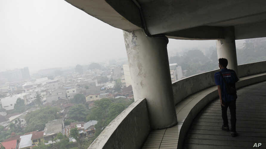 A man walks in a building as haze from wildfires blanket the city Medan, North Sumatra, Indonesia, Tuesday, Oct. 6, 2015.