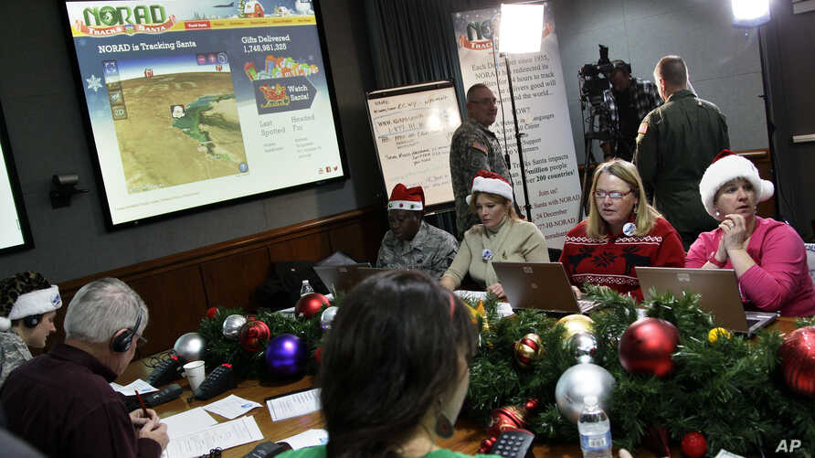 Volunteers take phone calls from children asking where Santa is and when he will deliver presents to their house, during the annual NORAD Tracks Santa Operation, at the North American Aerospace Defense Command, or NORAD, at Peterson Air Force Base, i