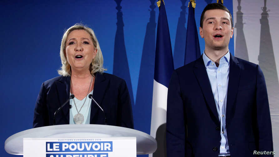 French far-right National Rally (Rassemblement National) party leader Marine Le Pen and Jordan Bardella, the head of the National Rally list for the European elections, sing the national anthem during a meeting in Saint-Paul-du-Bois, France, Feb. 17,