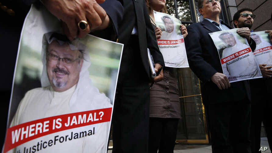 Alyssa Edling, center, and Thomas Malia, second from right, both with PEN America, join others as they hold signs of missing journalist Jamal Khashoggi, during a news conference about his disappearance in Saudi Arabia, Oct. 10, 2018, in front of The