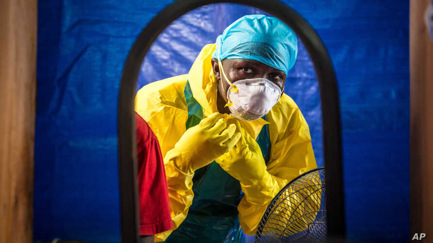 FILE - a healthcare worker dons protective gear before entering an Ebola treatment center in the west of Freetown, Sierra Leone.