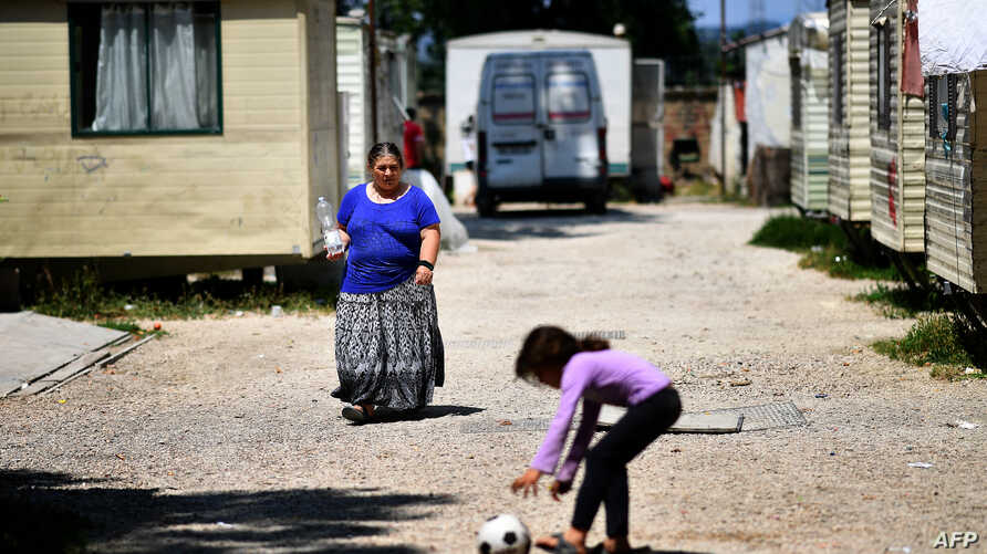 """A woman, member of the Roma community, walks at the """"River Village"""" Roma camp, managed by the Onlus Isola Verde association, June 19, 2018, on the outskirts of Rome, Italy."""