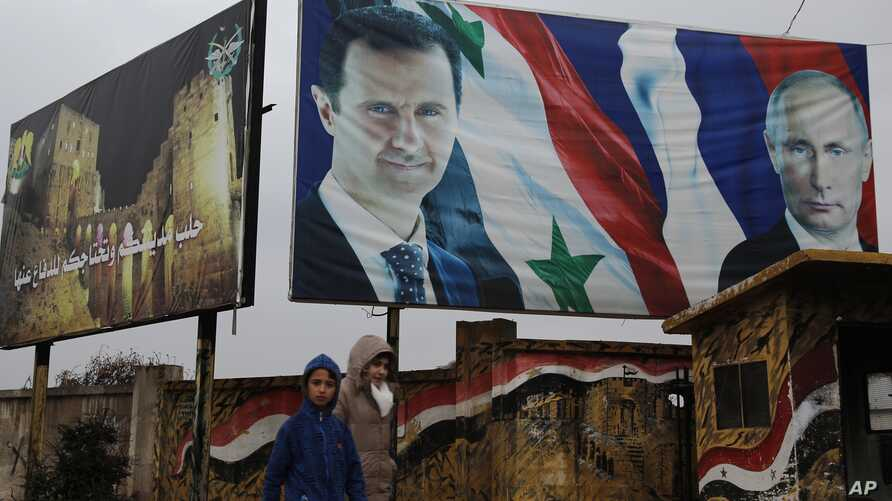 FILE - Syrian walk by posters of Syrian President Bashar al-Assad and Russian President Vladimir Putin in Aleppo, Syria, Jan. 18, 2018.