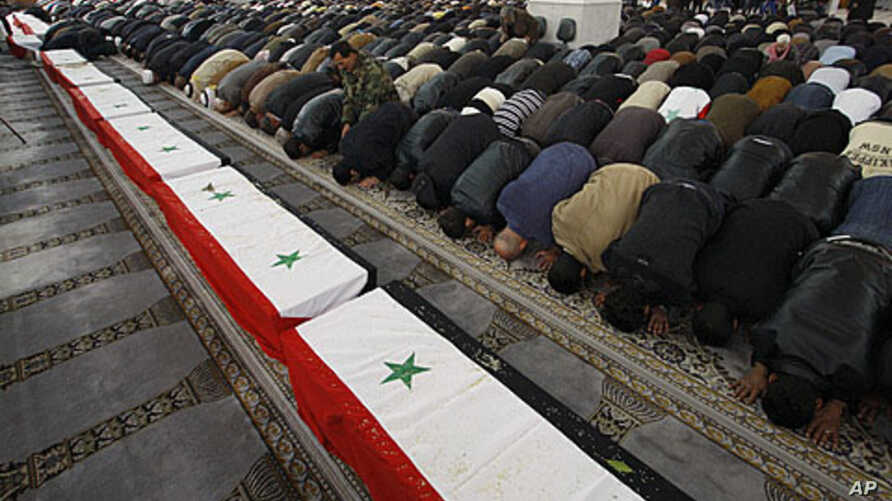 Syrian mourners pray in front of the coffins of 11 Syrian police officers who were among those killed in an explosion in the Midan district of Damascus Friday, during a mass funeral at Al-Hassan mosque in the Syrian capital Saturday, January 7, 2012.