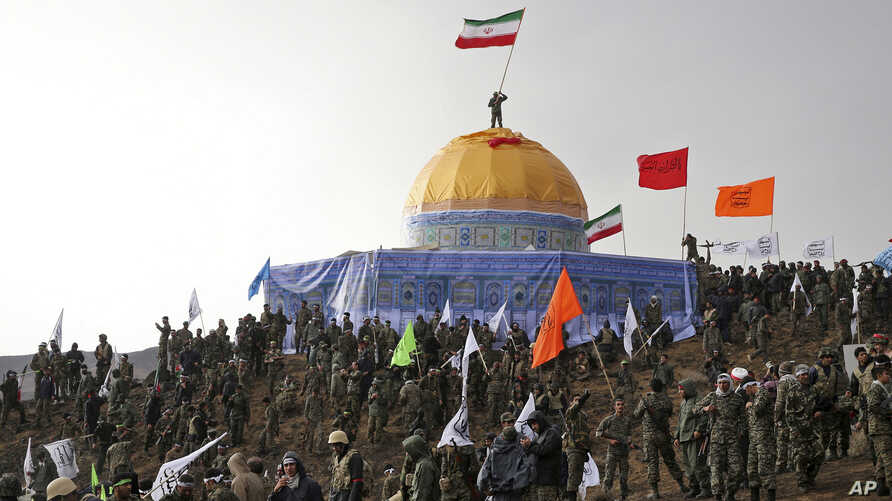 Members of the Basij, the paramilitary unit of Iran's Revolutionary Guard, gather around a replica of Jerusalem's gold-topped Dome of the Rock mosque as one of them waves an Iranian flag from on top of the dome during a military exercise, Nov. 20, 20...