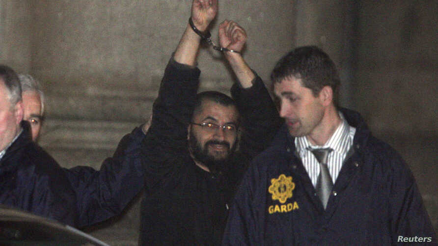 "FILE - Ali Charaf Damache, also known by the alias ""Black Flag,"" is accompanied by Irish law enforcement officials as he appears at Waterford District Court to be remanded into custody after being arrested on terrorism charges in Waterford, Ireland,"