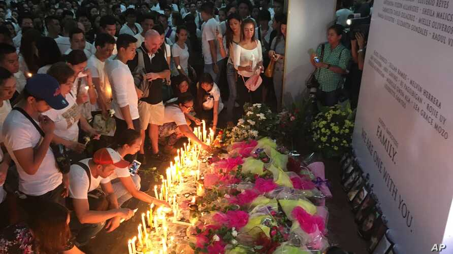 Mourners in the Philippine capital, Manila, light candles and lay flowers in front of a memorial outside the Resorts World Manila entertainment complex, June 3, 2017.  On Friday, a gunman entered the complex and set fire to its casino, triggering a b