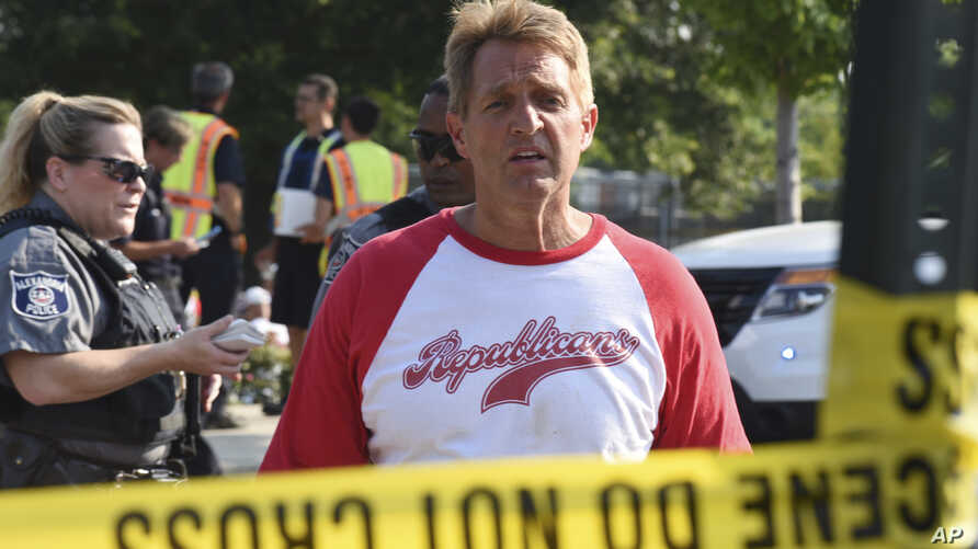Sen. Jeff Flake, R-Ariz. walks toward media gathered at the scene of a shooting at a baseball field in Alexandria, Va., June 14, 2017, during a Congressional baseball practice where House Majority Whip Steve Scalise of La. was shot.