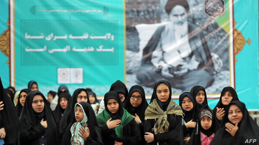 Iranian women pray in front of a a poster of Iran's late founder of the Islamic Republic, Ayatollah Ruhollah Khomeini, on the occasion of 40th anniversary of Khomeini's return from exile from Paris at his mausoleum in southern Tehran, Feb. 01, 2019.