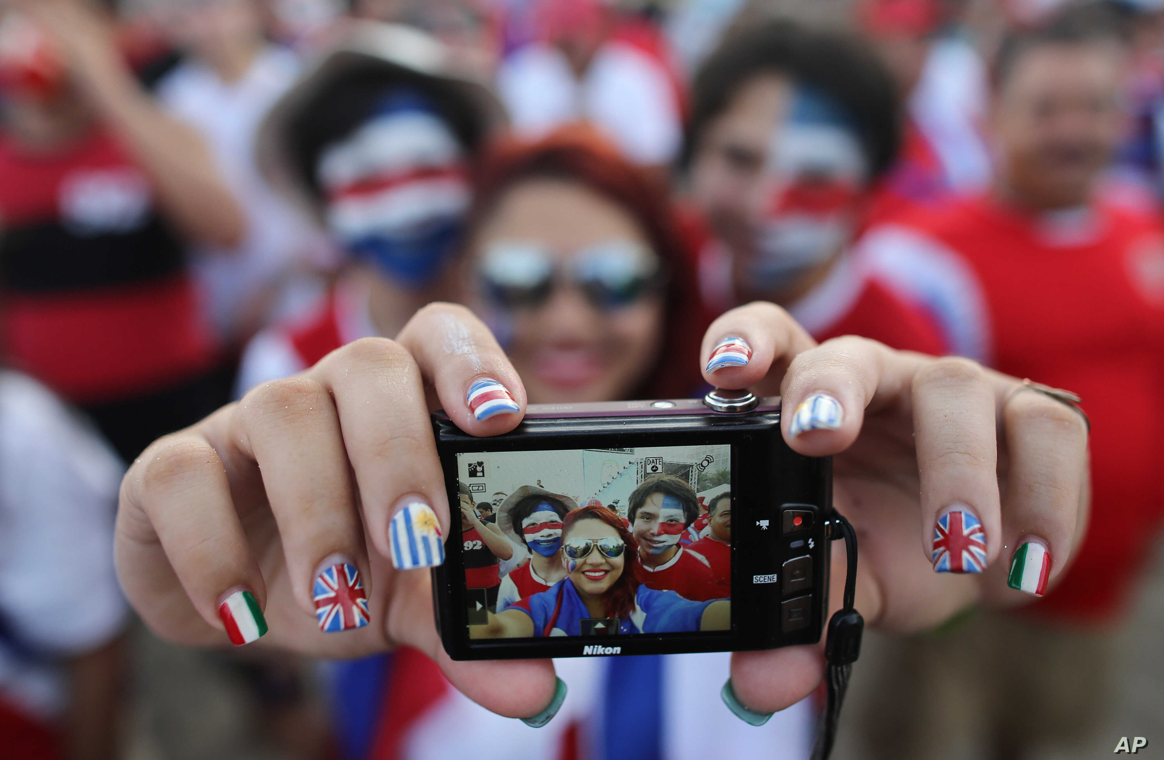 Costa Rica soccer fans pose for a selfie before watching their team's World Cup round of 16 match against Greece on a live telecast inside the FIFA Fan Fest area on Copacabana beach in Rio de Janeiro, Brazil, June 29, 2014.