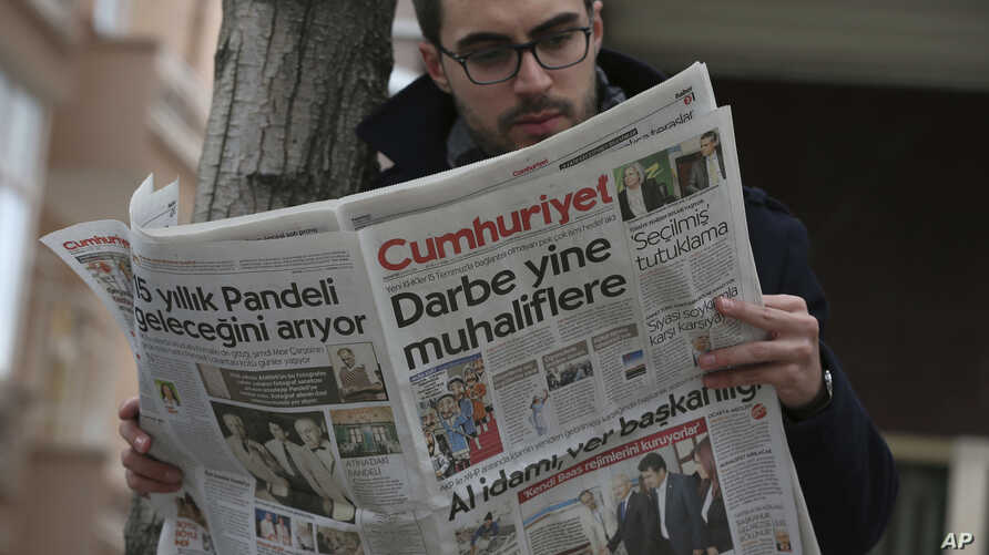 """A man reads Cumhuriyet newspaper outside its Ankara office after Turkish police detained the chief editor and at least eight senior staff of Turkey's opposition newspaper, Oct. 31, 2016.The headline reads: """"the coup against opposition again."""""""