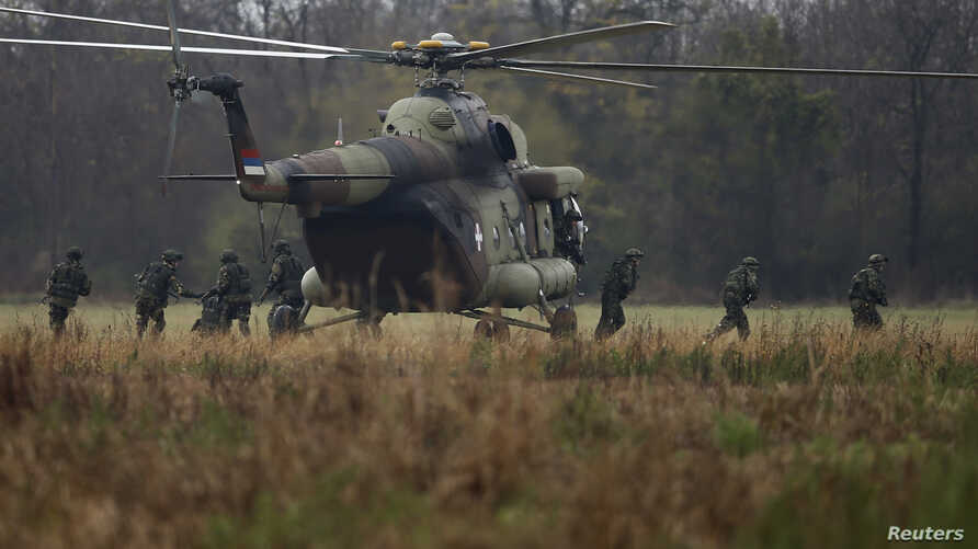 FILE - Serbian soldiers disembark from an MI-8 helicopter during a military training exercise in the town of Kovin, near Belgrade, Serbia, Nov. 7, 2016.