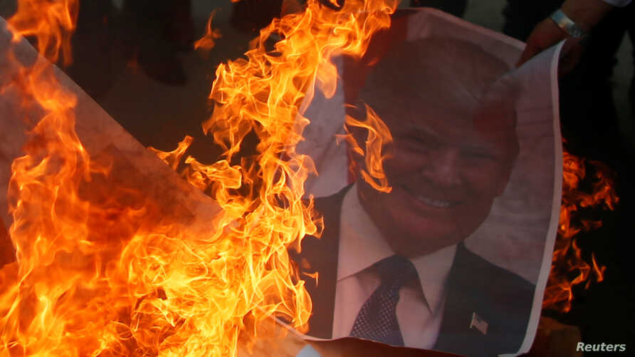 A Palestinian protester burns a poster depicting U.S. President Donald Trump during a protest against Trump's decision to recognize Jerusalem as the capital of Israel, in Gaza City, Dec. 7, 2017.