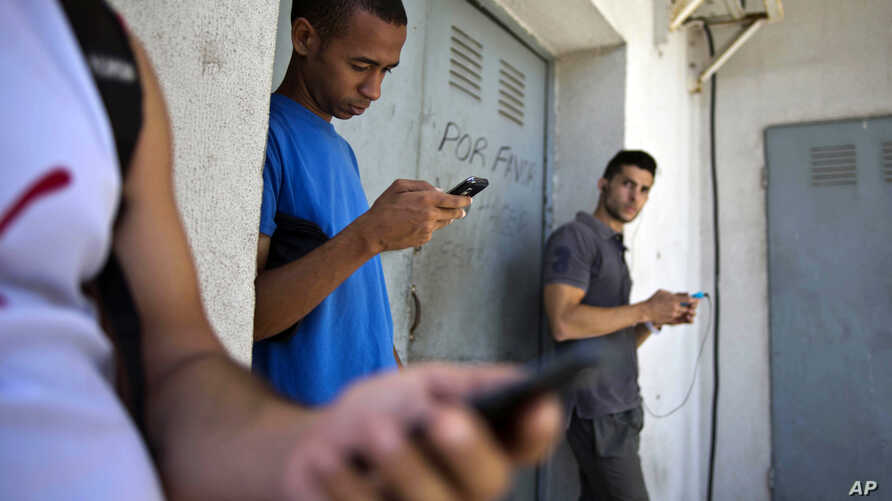Students gather behind a business looking for a Internet signal for their smart phones in Havana, Cuba, April 1, 2014.