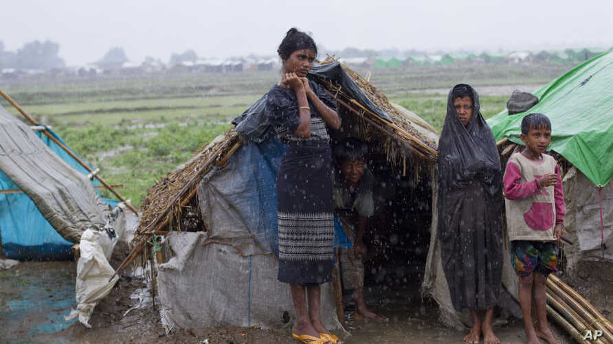 Internally displaced Rohingya stand outside their makeshift tent in a camp in Sittwe, northwestern Rakhine State, Burma, May 14, 2013.