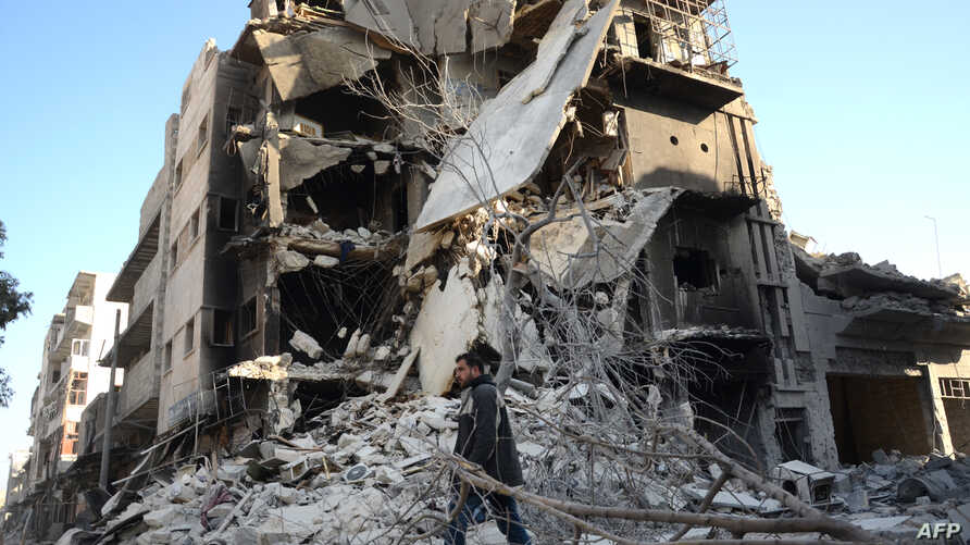 FILE - A Syrian man walks past a damaged building in the northwestern border town of al-Bab on Feb. 25, 2017 after Turkish-backed rebels announced the recapture of the town from the Islamic State (IS) group earlier in the week