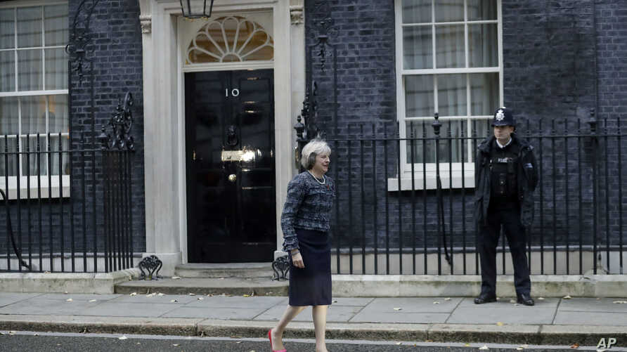 FILE - British Prime Minister Theresa May is seen walking outside 10 Downing Street in London, Nov. 9, 2016. A legislative aide was photographed in Downing street carrying hand-written notes some say offer insights into London's Brexit strategy.