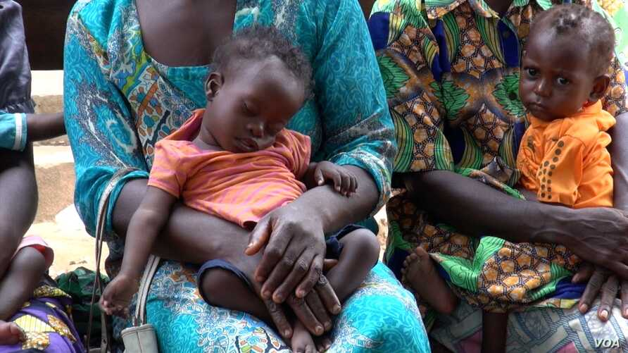 Fourteen-month-old Georgette Lukaji rests in her mother's lap as she and other children wait to be treated at a roadside UNICEF clinic, in Kananga, Democratic Republic of Congo. (A. Powell/VOA)