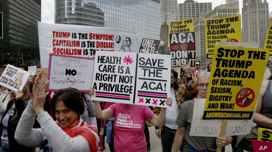 Protesters gather across the Chicago River from Trump Tower to rally against the repeal of the Affordable Care Act Friday, March 24, 2017, in Chicago.