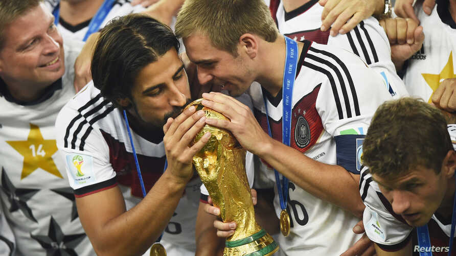Germany's Sami Khedira (L) and Philipp Lahm (2nd R) kiss the World Cup trophy as they celebrate at the end of the 2014 World Cup final between Germany and Argentina at the Maracana stadium in Rio de Janeiro, July 13, 2014.