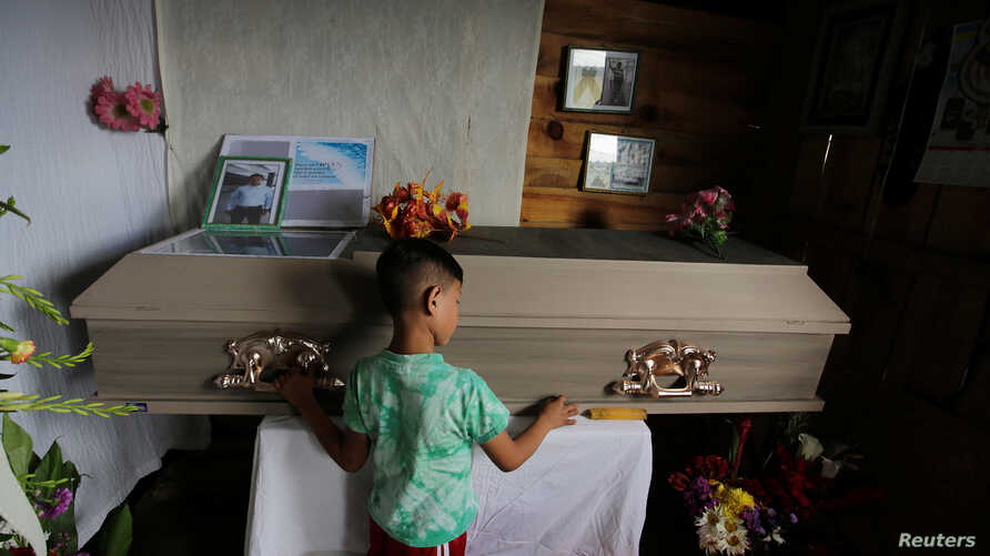 A child touches the coffin of Nelson Espinal, 28, Dec. 19, 2018. Espinal was shot to death the night before shortly after leaving his home in Tegucigalpa, Honduras.