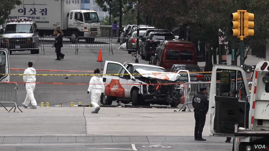 Investigators work around wreckage of Home Depot pickup truck that alleged terror suspect Sayfullo Saipov used to mow down people on a bike path in New York City, Nov. 1, 2017. (Photo: R. Taylor / VOA)