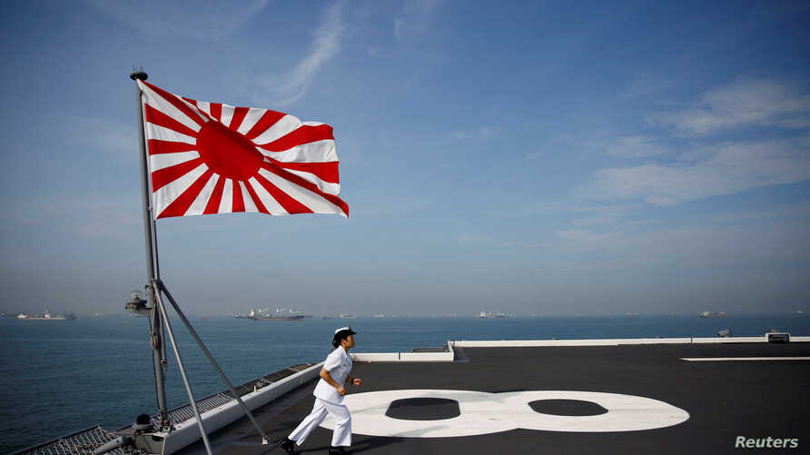Yuma Osaki, a navigator, runs back to her post after a flag-raising ceremony on the flight deck of Japanese helicopter carrier Kaga before its departure for naval drills in the Indian Ocean, Indonesia, Sept. 22, 2018.