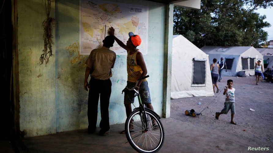 Venezuelans look at a map of the city of Boa Vista outside a gym which has turned into a shelter for Venezuelans in Boa Vista, Brazil Nov. 18, 2017.