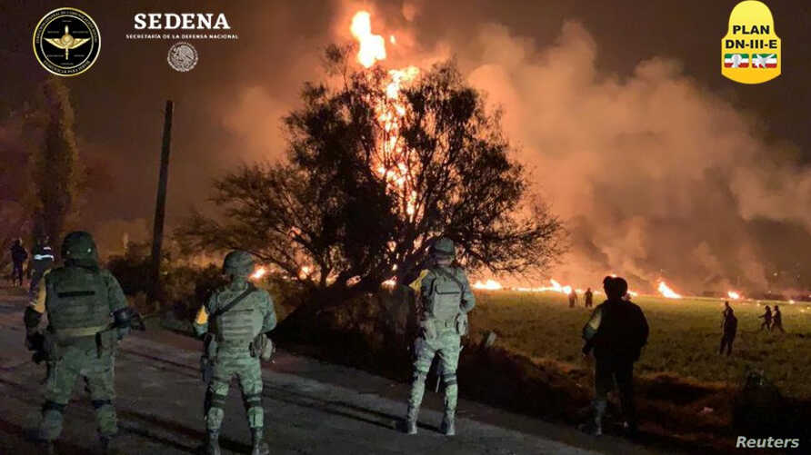 Military personnel watch as flames engulf an area after a ruptured fuel pipeline exploded, in the municipality of Tlahuelilpan, Hidalgo, Mexico, near the Tula refinery of state oil firm Petroleos Mexicanos (Pemex), Jan. 18, 2019.