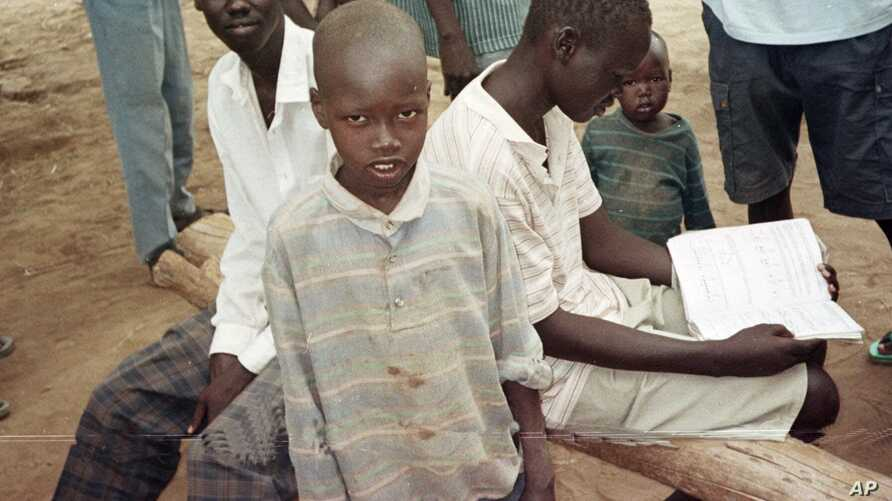 FILE - Sudanese boys pass the time in the Kakuma camp, in northern Kenya, April 24, 2000. Over 20,000 boys who were displaced or orphaned during two decades of civil war endured many hardships as they traveled on foot to refugee camps in Ethiopia and
