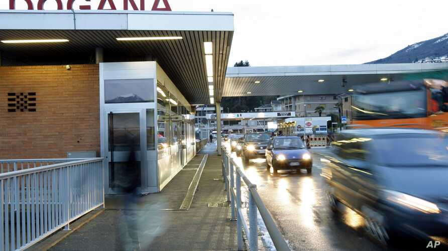 FILE - Cars pass the customs facilities in Ponte Tresa at the border between Switzerland and Italy, Friday, Dec 12, 2008.