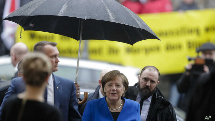 German Chancellor Angela Merkel, center, arrives for exploratory talks about a new German government between her Christian Unions block and the Social Democratic Party at the SPD headquarters in Berlin, Jan. 11, 2018.