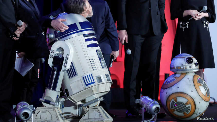 "Mark Hamill, a cast member of the movie ""Star Wars: The Last Jedi,"" hugs character R2-D2 during  promotional event in Tokyo, Dec. 6, 2017."