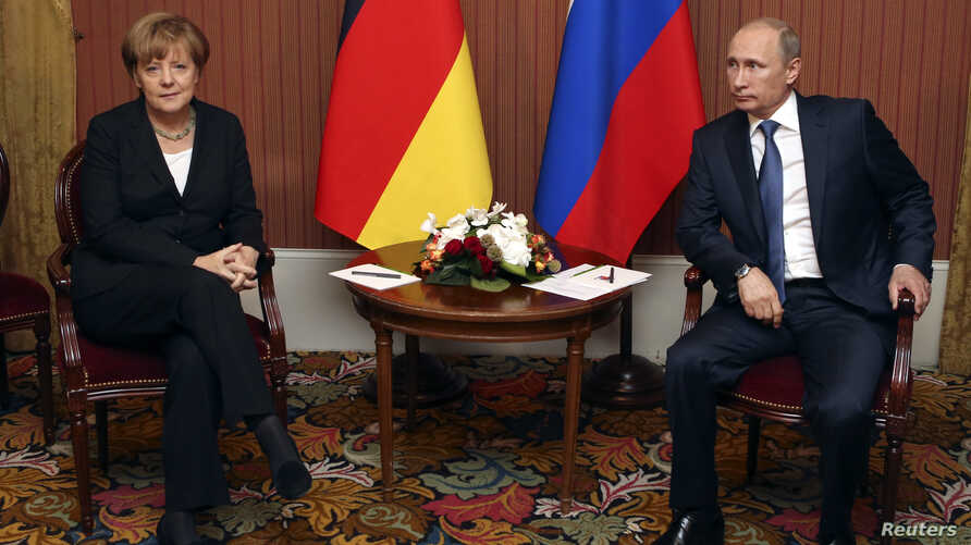 FILE - Russian President Vladimir Putin meets with German Chancellor Angela Merkel in Deauville, Northern France, June 6, 2014.